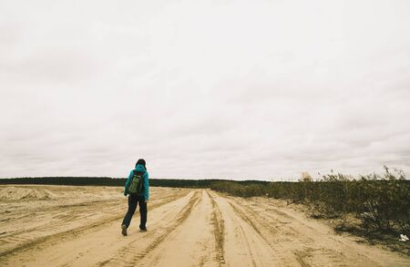 Young Woman Hiking Along Dirt Road, Rear View
