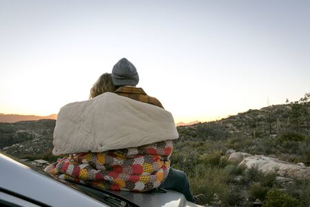 Rear View Of Young Couple By Mountains On Car Bonnet Wrapped In Patchwork Blanket, Chilao Campgrounds, Los Angeles, California, Usa