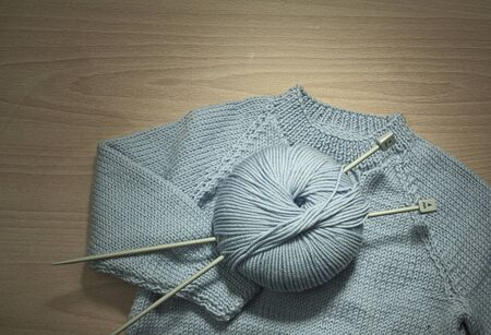 Blue Knitted Sweater With Ball Of Yarn And Knitting Needles