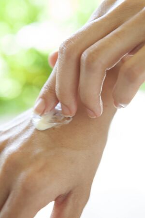 Close Up Of Woman Moisturising Hand With Fingers Using Moisturising Cream