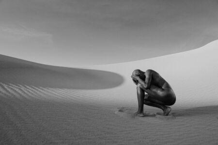 Nude Woman Cowering In Desert Stok Fotoğraf