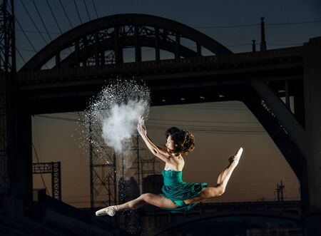 Young Female Dancer Leaping Whilst Releasing Powder Explosion At Sunset, Los Angeles, Usa