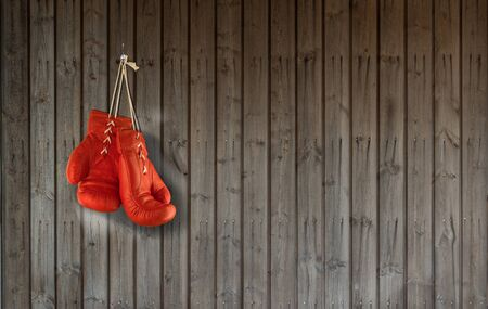 Pair Of Red Boxing Gloves Hanging From Wood Panelled Wall