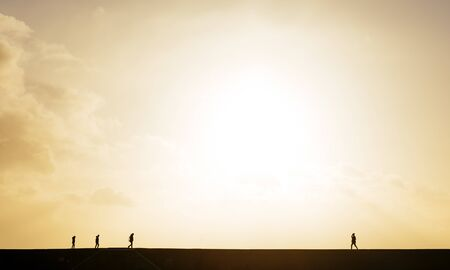 Silhouetted View Of People Strolling On 'The Cobb' Harbour Wall At Sunset, Lyme Regis, Dorset, England