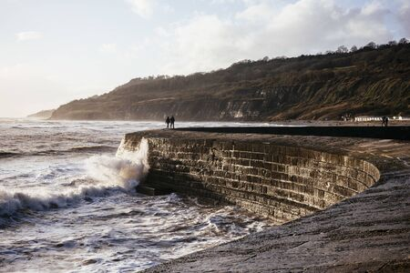 Two People Looking Out At Stormy Sea From 'The Cobb' Harbour Wall, Lyme Regis, Dorset, England Imagens