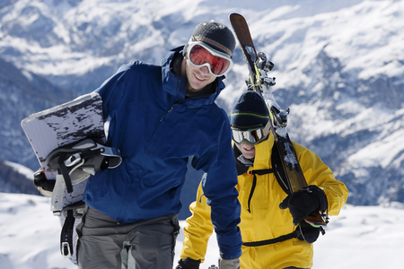 Male skier and male snowboarder walking up mountain ridge carrying skis LANG_EVOIMAGES