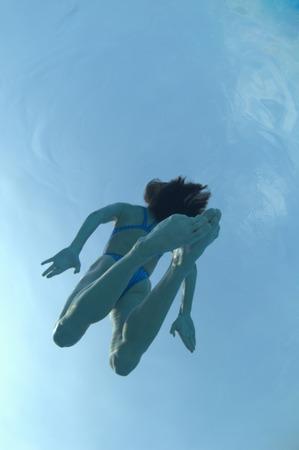 Woman floating in swimming pool, underwater view
