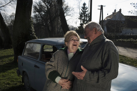 appearance: Senior couple leaning on car in countryside, smiling