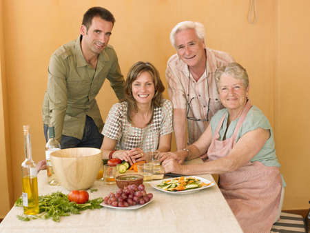 50 something: Senior couple preparing food at home with adult offspring, smiling, portrait