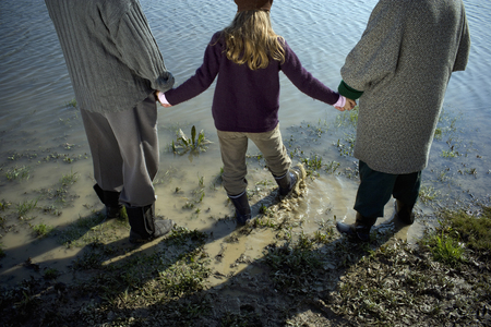 Grandparents holding hands with granddaughter (10-12) by river