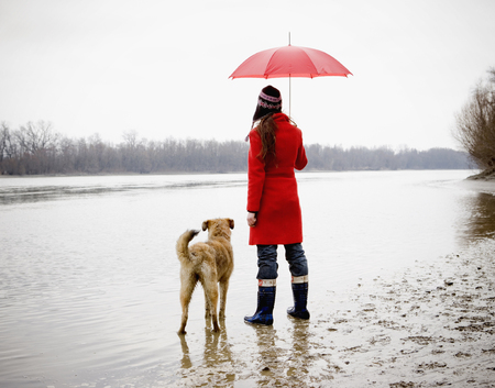 Young woman holding umbrella, standing by river with dog, rear view LANG_EVOIMAGES