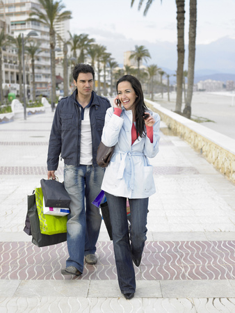 Couple walking along palm lined pavement, man carrying shopping bags while woman talks on mobile phone. Alicante, Spain.