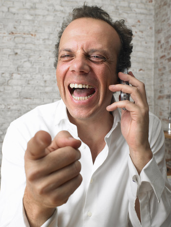 Businessman on the phone pointing at camera and laughing. ,Brussels, Belgium.