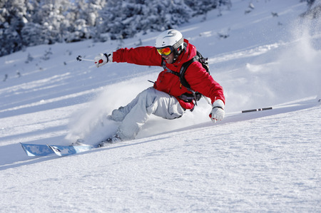 Austria, Saalbach, man skiing down slope, smiling LANG_EVOIMAGES