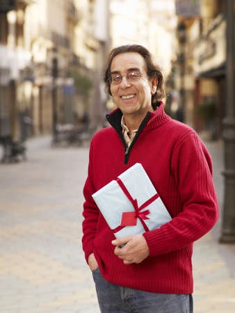 50 something: Mature man standing in street holding gift, smiling, portrait