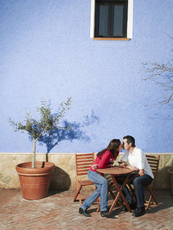 be kissed: Couple sitting on garden terrace, kissing