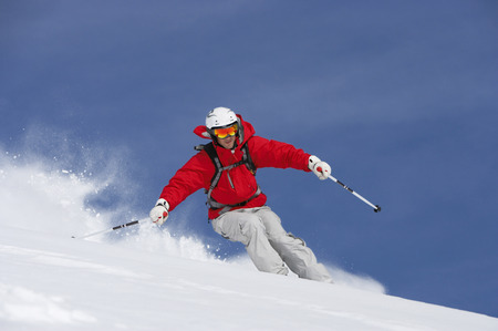 Man skiing down snow covered slope, low angle view