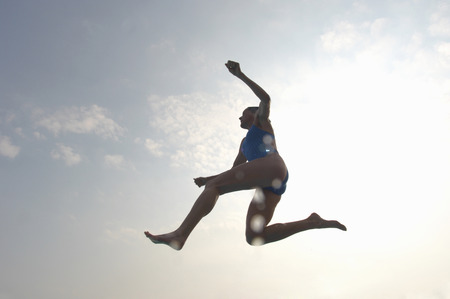 Woman wearing swimming costume jumping, low angle view