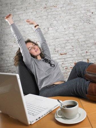 appearance: Businesswoman stretching with feet up on desk. ,Brussels, Belgium. LANG_EVOIMAGES