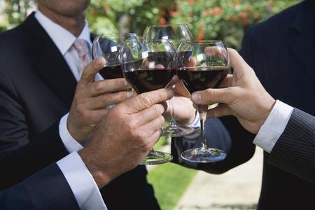 Four businessmen drinking wine in a garden LANG_EVOIMAGES