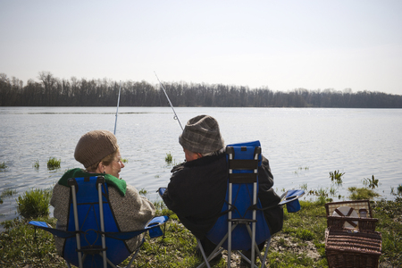 Senior couple fishing together by river, rear view