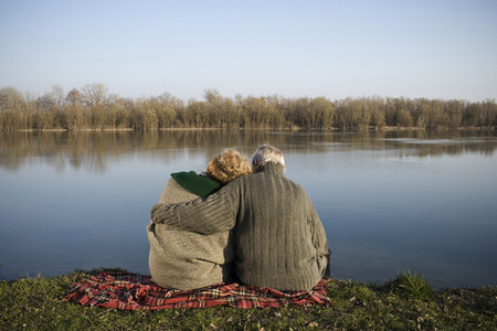 appearance: Senior couple sitting on rug by river, rear view
