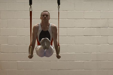 Male gymnast balancing on rings LANG_EVOIMAGES