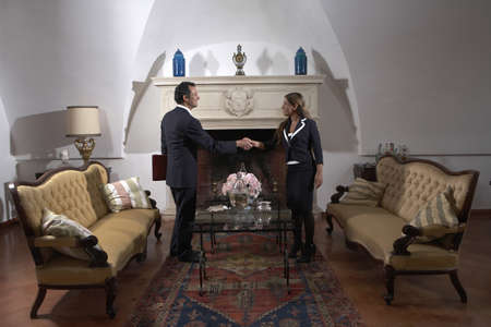 thirtysomething: Businessman shaking hands with woman in living room