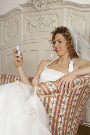 young bride smiling looking at mobile phone LANG_EVOIMAGES