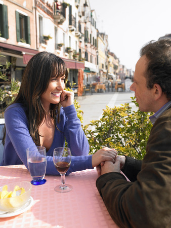 appearance: Couple holding hands at outdoor restaurant. Venice, Italy.