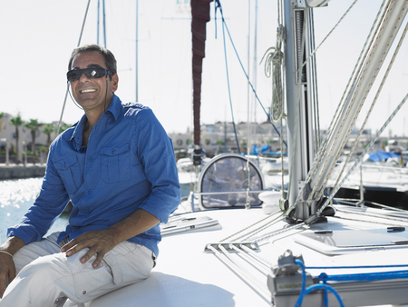 attainment: Mature man wearing sunglasses sitting on yacht, smiling LANG_EVOIMAGES
