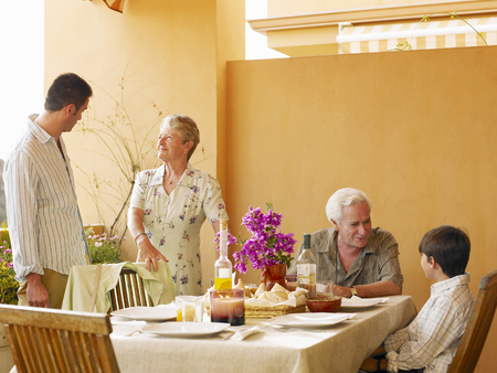Multi-generational family talking at dining table on balcony
