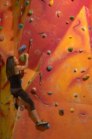 thirtysomething: Woman climbing indoor wall
