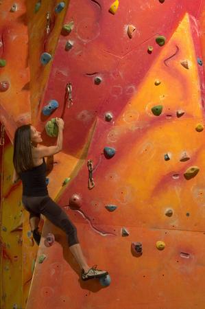 experiencing: Woman climbing indoor wall
