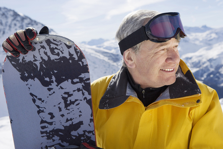 Mature male snowboarder on mountain, close-up, portrait