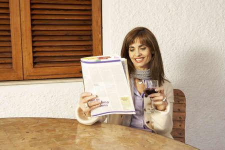 passtime: Woman reading magazine holding glass of wine