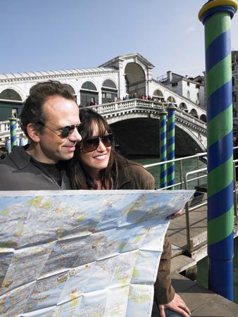 shadowed: Couple reading map by Rialto Bridge. Venice, Italy.
