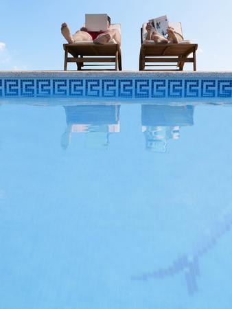 Couple sunbathing by swimming pool, man using laptop