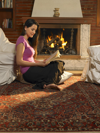 Young woman reading on rug in front of fire. Alicante, Spain.