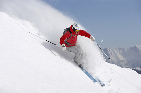 Austria, Saalbach, male skier turning in snow on slope