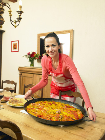 formulate: Young woman putting large dish of paella on dining table, smiling, portrait