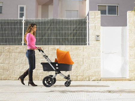 single dwellings: Mother pushing pram on pavement, Alicante, Spain,