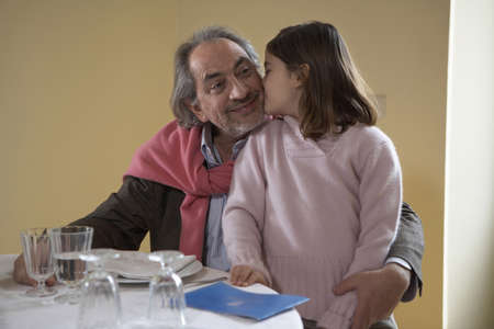 be kissed: Girl (6-8) kissing grandfather at dinner table
