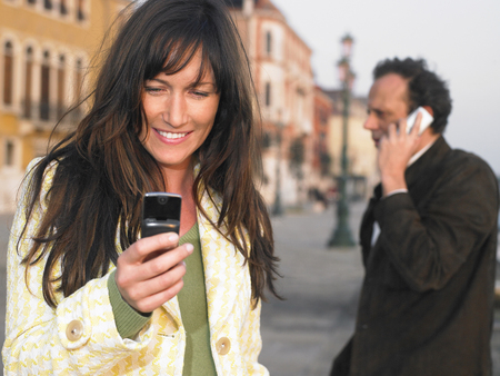 appearance: Man and woman using mobile phones. Venice, Italy. LANG_EVOIMAGES