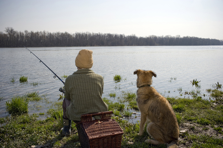 k9: Boy (12-14) fishing by river with pet dog, rear view
