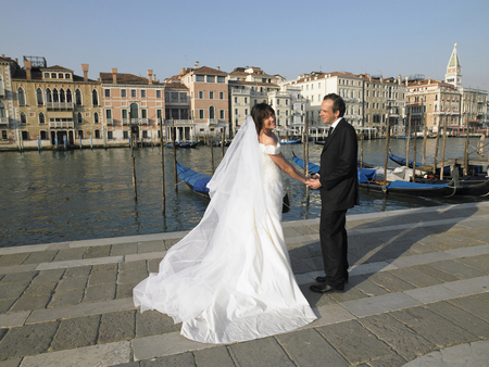 Bride and groom holding hands. Grand Canal, Venice, Italy.
