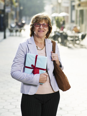 passtime: Mature woman standing in street holding gift, smiling, portrait