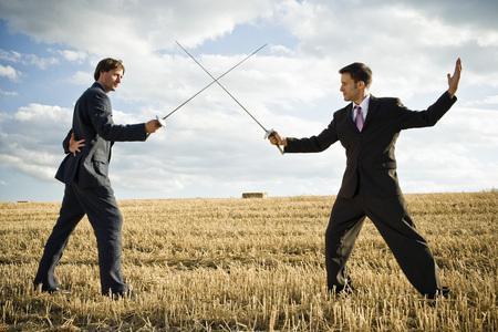 Businessmen fencing in wheat field.