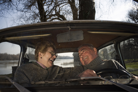 Senior couple sitting in car, smiling at each other