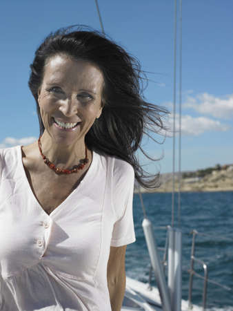 50 something: Mature woman standing on yacht, smiling, portrait